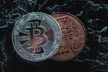 close up view of arranged silver and bronze bitcoins on dark marble surface