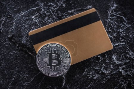 top view of credit card and silver bitcoin on dark marble tabletop