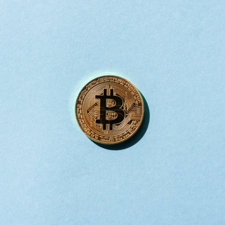 top view of golden bitcoin on blue background