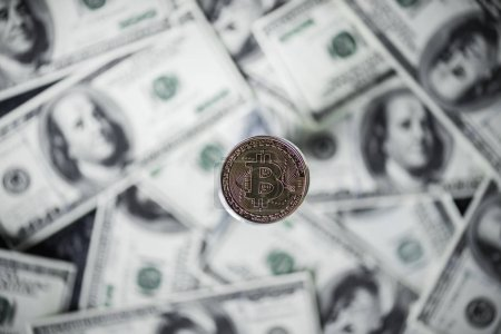 selective focus of silver bitcoin and dollar banknotes on background