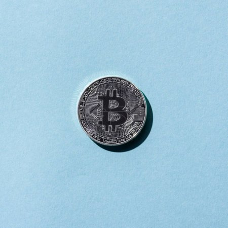 top view of silver bitcoin on blue background