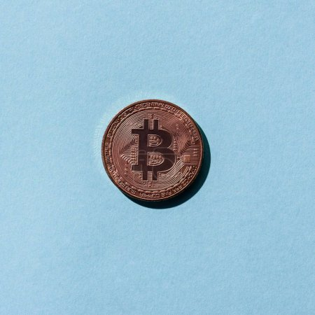 top view of bronze bitcoin on blue background