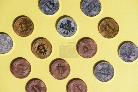 top view of arranged various bitcoins on yellow tabletop