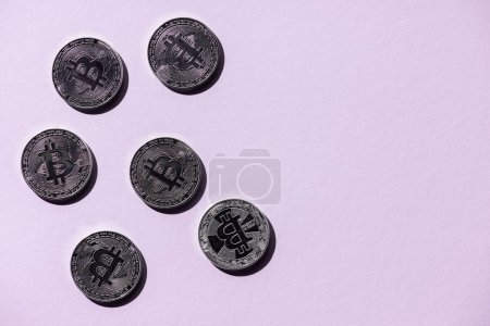 top view of arranged silver bitcoins on purple background
