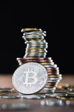 selective focus of silver bitcoin and piles of bitcoins behind
