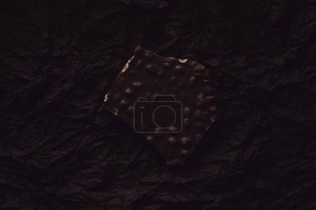 Photo for Top view of chocolate with pieces of nuts on surface covering by black crumpled paper - Royalty Free Image