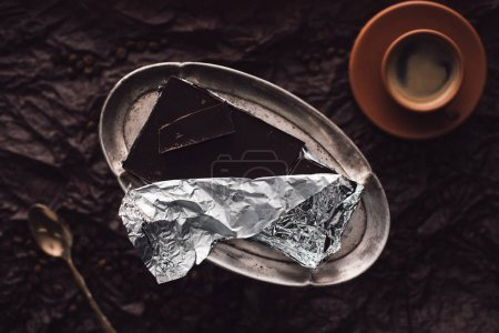 top view of coffee cup, spoon and chocolate in foil on silver trail surrounded by coffee grains on surface covering by black crumpled paper
