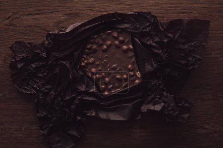 top view of chocolate with nuts in black crumpled paper on wooden table