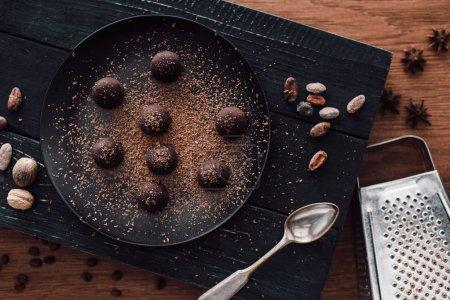 Foto de Vista elevada de tablero de corte con trufas en placa de cubierta de chocolate rallado, cuchara, cacao en grano, nuez moscada, anís y rallador sobre mesa de madera - Imagen libre de derechos