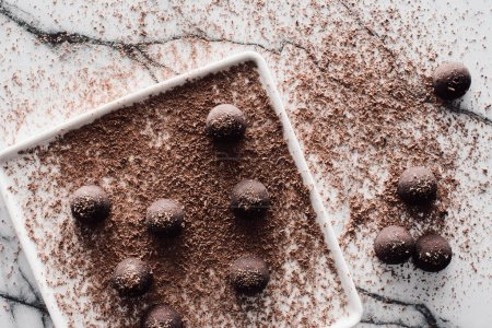 top view of plate with truffles covering by grated chocolate on marble table