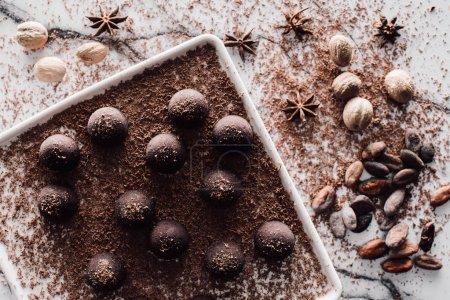 Foto de Vista superior de la placa con trufa cubierta de chocolate rallado, cacao en grano, anís y nuez moscada en mesa de mármol - Imagen libre de derechos
