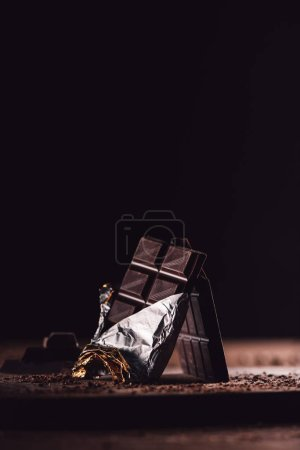 closeup shot of two arranged chocolate bars on wooden table on black background