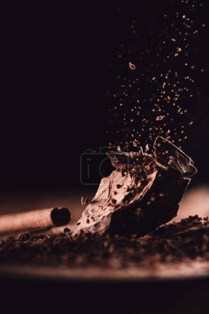 closeup shot of cinnamon stick and grated chocolate falling on pieces of chocolate on black background