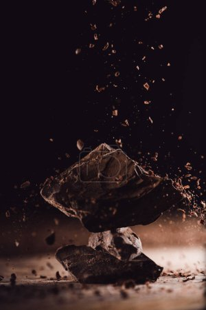 close up image of grated chocolate falling on pieces of chocolate on black background
