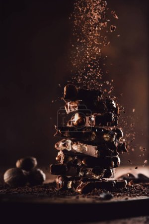 Photo for Closeup view of nutmegs and grated chocolate falling on stack of chocolate pieces on wooden table - Royalty Free Image