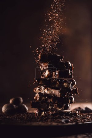 Photo for Close up shot of nutmegs and grated chocolate falling on stack of chocolate pieces on wooden table - Royalty Free Image
