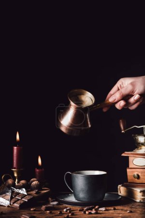 partial view of woman pouring coffee from turk into cup at table with chocolate, truffles, candles and coffee grains on black background