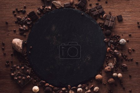 Photo for Elevated view of cutting board surrounded by various types of chocolate pieces, truffles. coffee grains and cocoa beans on wooden table - Royalty Free Image