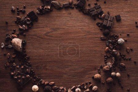 Foto de Vista superior del círculo de varios tipos de piezas de chocolate, trufas, granos de café y cacao en mesa de madera - Imagen libre de derechos
