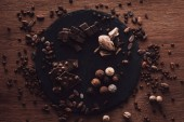 elevated view of cutting board with various types of chocolate pieces and truffles surrounded by cocoa beans, coffee grains and nutmegs on wooden table