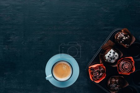Top view of delicious muffins with glaze and blue cup of coffee on wooden background
