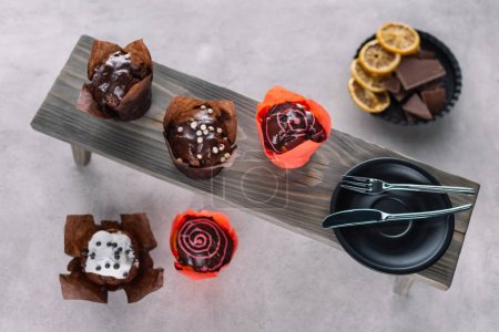 Sweet chocolate muffins and cutlery on wooden background