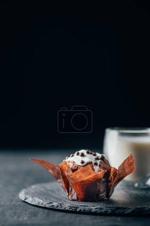 süße Muffins mit Schokoladenstücken und einem Glas Milch auf Schiefertafel