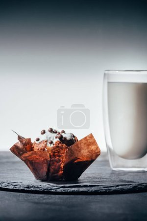 Sweet cupcake with chocolate chips and glass of milk on slate board