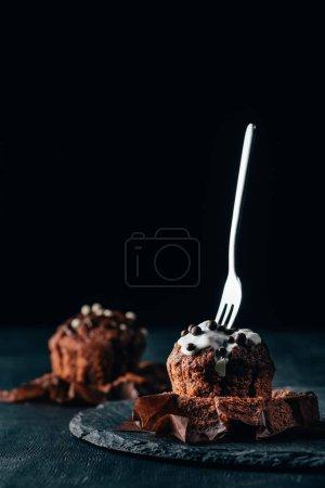 Photo pour Cupcakes sucrés avec pépites de chocolat et fourchette sur fond sombre - image libre de droit