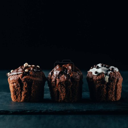 Sweet muffins with chocolate chips on dark background