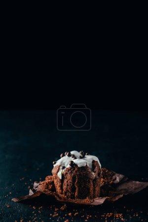 Sweet chocolate muffin with glaze on dark background