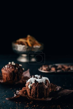 Sweet cupcakes with chocolate chips and sweet glaze on dark background