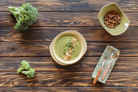 top view of vegetarian cream soup with broccoli, sprouts and almonds in bowl on wooden tabletop