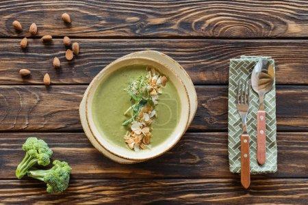 Draufsicht auf vegetarische Sahnesuppe mit Brokkoli, Rosenkohl und Mandeln in Schüssel auf Holztischplatte