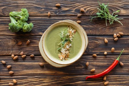 top view of arranged vegetarian cream soup, fresh broccoli, almonds and chili peppers on wooden surface
