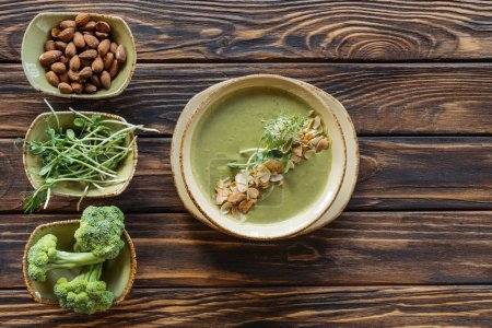 top view of arranged vegetarian cream soup, sprouts, almonds and fresh broccoli in bowls on wooden surface