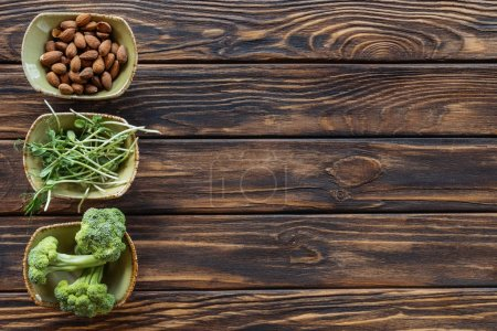 top view of almonds, fresh broccoli and sprouts in bowls on wooden tabletop