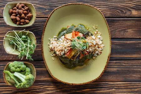 top view of vegetarian salad served on plate and fresh ingredients in bowls on wooden tabletop