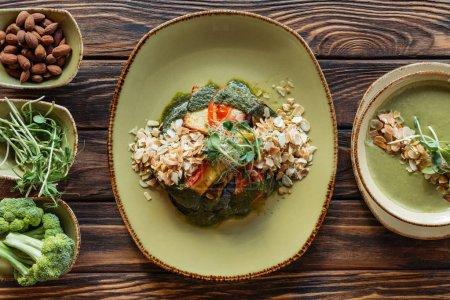 lay plat avec arrangement de salade végétarienne, velouté et ingrédients autour sur la surface en bois
