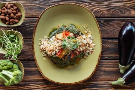 vue de dessus de salade végétarienne avec amande râpée servis sur plaque et ingrédients frais disposées autour sur table en bois