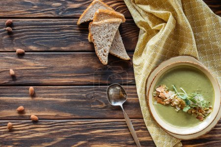 top view of arrangement of vegetarian cream soup with sprouts, pieces of bread and almonds on wooden surface