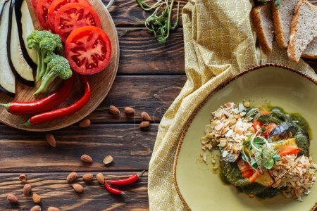 Photo for Flat lay with vegetarian salad, almonds, chili peppers, fresh vegetables and pieces of bread on wooden tabletop - Royalty Free Image