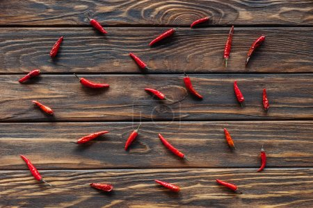 Photo for Top view of arranged chili peppers on wooden surface - Royalty Free Image