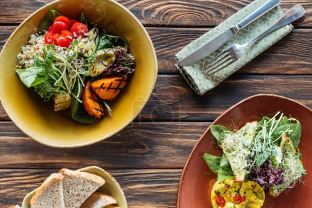 Photo for Flat lay with vegetarian salads served in bowls and cutlery on wooden tabletop - Royalty Free Image