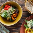 Flat lay with vegetarian salads served in bowls, p...