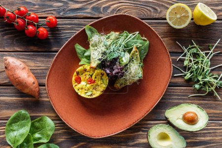 flat lay with vegetarian salad served on plate and fresh ingredients arranged around on wooden tabletop