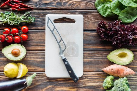 flat lay with cutting board with knife and fresh vegetables arranged around on wooden tabletop