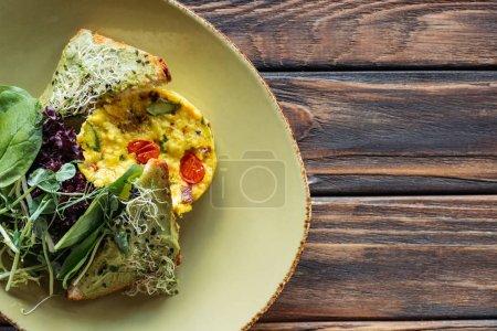 Photo pour Vue du dessus de la salade végétarienne aux épinards et germes sur plateau en bois - image libre de droit
