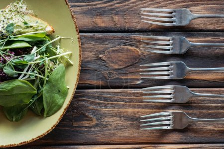 top view of vegetarian salad and arranged forks on wooden surface