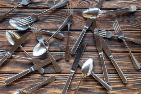 top view of arranged steel cutlery on wooden tabletop